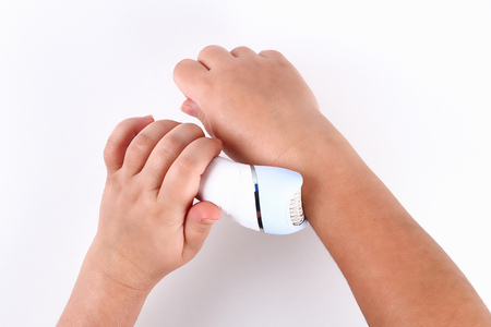 Girl removes hair with an electric epilator in her hands on a white background. Top view.