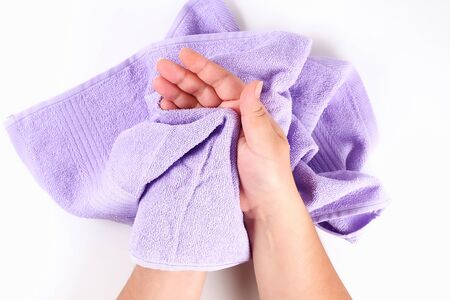 Girl wipes her hands with a purple towel on a white background. Top view.