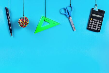 School supplies hang on the rope. School supplies on blue background. Back to school concept Фото со стока - 124990936