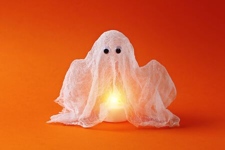 14 Diy Halloween ghost of starch and gauze on orange background. Gift idea, decor Halloween. Step by step. Top view. Process kid children Halloween craft. Workshop. Фото со стока
