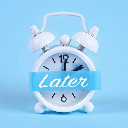 Concepto de dilación, demora y urgencia. Despertador blanco con una nota adhesiva con texto más tarde.