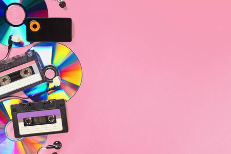 The concept of the evolution of music. Cassette, CD-disk, mp3 player on pink background. Vintage and modernity. Music support