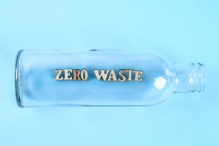 Zero waste concept. Empty glass bottle for zero waste shopping and storage on blue background. No plastic. Zero waste tips. Eco lifestile.