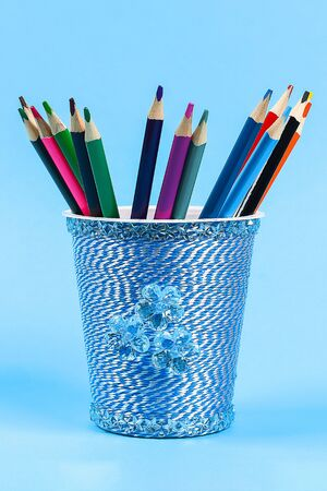 Diy pencil holder plastic glass sour cream, yogurt wrapped thread blue background. Decoration flower hot glue, decorative sticky tape. Gift idea. Step by step. Top view. Process kid childrens craft