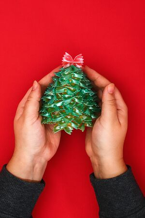 How to make a Christmas tree from raw pasta bows. The process of making Christmas trees from pasta, cardboard plates, hot glue and paint or spray. Guide, step by step on the photo. Handmade, DIY Stockfoto