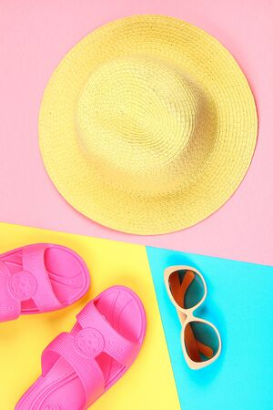 Hat, sunglasses and slippers on a three-color pastel background of blue, yellow and pink