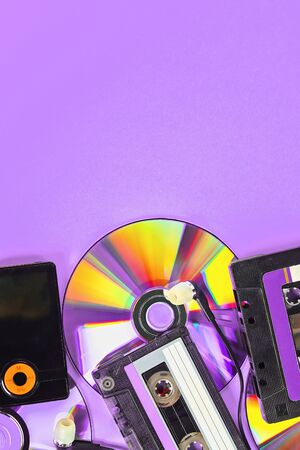 The concept of the evolution of music. Cassette, CD-disk, mp3 player on violet background. Vintage and modernity. Music support