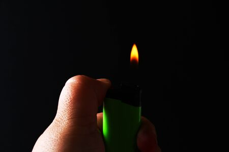 Hand holding burning gas lighters on dark black background. Portable device used to create a flame. Close up