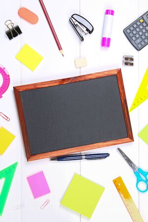 Chalkboard surrounded by stationery on a white wooden table. Copy the space 版權商用圖片