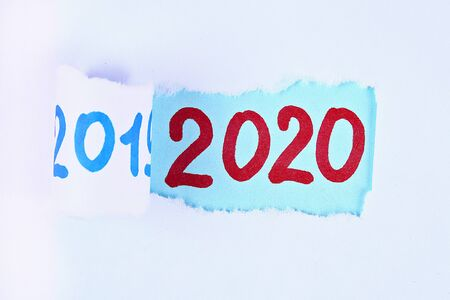 Torn piece paper revealing word new year 2020. Christmas. Business, finance, salary, crisis, and development concept. New year planing. 2020 goals. Stock Photo