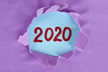 Torn piece paper revealing word new year 2020. Christmas. Business, finance, salary, crisis, and development concept. New year planing. 2020 goals. Stock Photo - 128246850