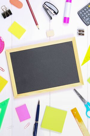 Chalkboard surrounded by stationery on a white wooden table. Copy the space Imagens