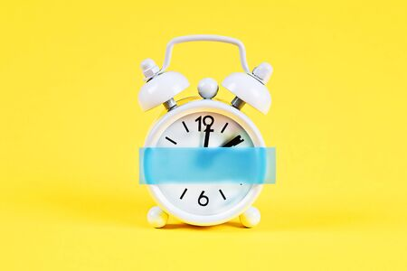 White alarm clock on yellow pastel background. Blank sticky note on the alarm clock for text. Reminder. Space for copy. Minimal concept. Stockfoto - 128246882