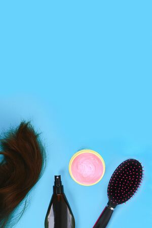 Hair, hair mask, comb, spray on a pastel blue background. The concept of hair care. Copy space, top view Zdjęcie Seryjne