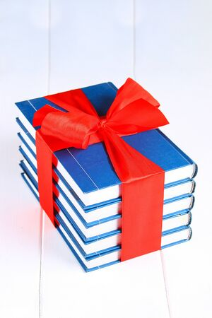 A pile of books tied with a red ribbon on a white wooden table. A gift on the background of a chalkboard Imagens