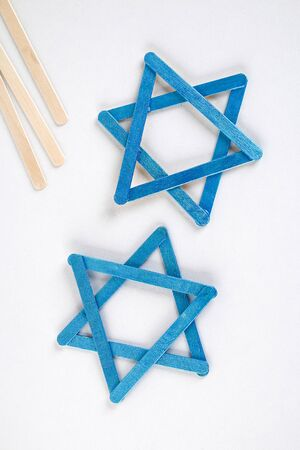 DIY. Hanukkah decor. Star of David from ice cream sticks on a white wooden table. Guide, step by step on the photo. Diy on Hanukkah