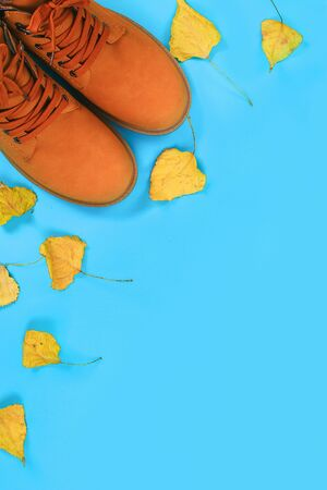 Orange brown mens autumn boots on a blue pastel background. Top view, copy space