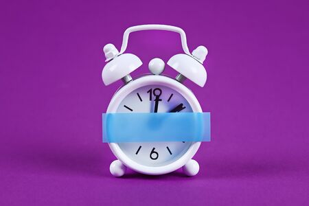White alarm clock on purple background. Blank sticky note on the alarm clock for text. Reminder. Space for copy. Minimal concept.