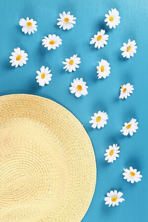 Straw hat with a camomile on a blue background. Top view. Summer background. Flat lay. Banco de Imagens