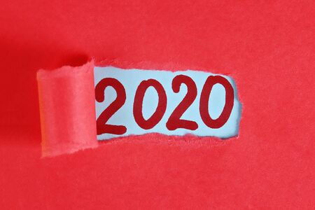 Torn piece paper revealing word new year 2020. Christmas. Business, finance, salary, crisis, and development concept. New year planing. 2020 goals. Banco de Imagens