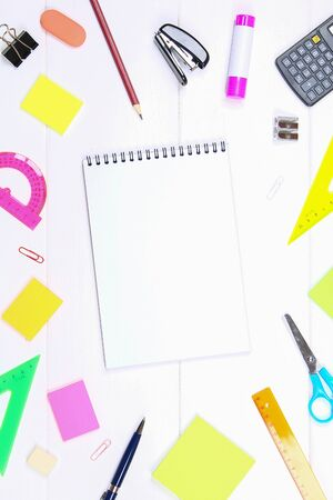 A blank notebook page surrounded by stationery on a white wooden table. Copy the space