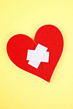 A red felt heart broken into two halves, glued together by a plaster on a yellow background