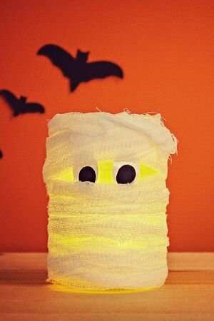 The concept for Halloween. Bats and mummy from a jar, bandages and candles on an orange background
