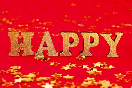 Text Happy laid out of gold letters on a beautiful background. Golden stars confetti. Banco de Imagens