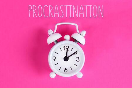 Procrastination, delay and urgency concept. White alarm clock with text procrastination.