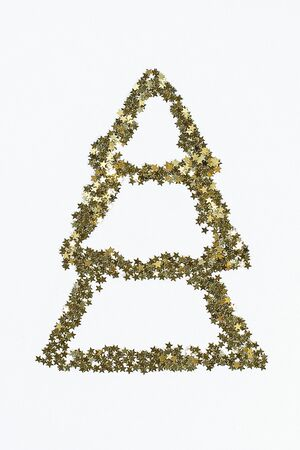 Christmas layout. Golden confetti in the form of stars folded in the shape of Christmas tree a white background. New Year 2020, christmas, winter concept. top view, flat lay composition
