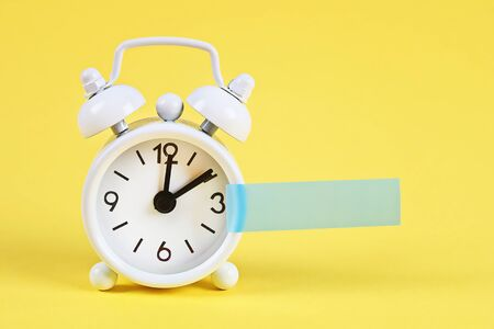 White alarm clock on yellow pastel background. Blank sticky note on the alarm clock for text. Reminder. Space for copy. Minimal concept.