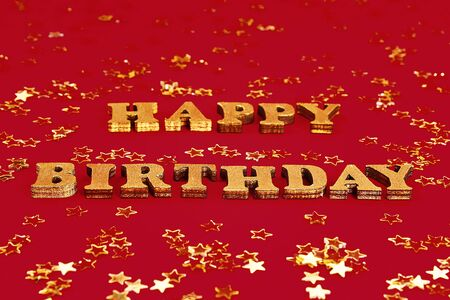 Text Happy birthday laid out of gold letters on a beautiful background. Golden stars confetti. Banco de Imagens