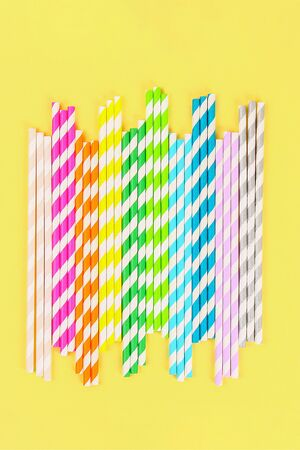 Multi-colored straw paper tubes on a bright yellow pastel background. Top view Banco de Imagens