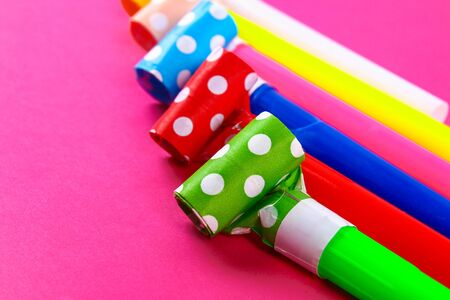 Multicolor party blowers on pink background. Multicolored party whistles. Decor for birthday.