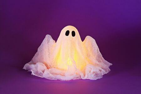 Halloween ghost of starch and gauze on ultraviolet background. Gift idea, decor Halloween. Process kid children Halloween craft. Workshop.