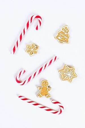 Christmas layout. Striped red-white cane candies and homemade ginger cookies on a white background. New Year 2020, christmas, winter concept. top view, flat lay composition