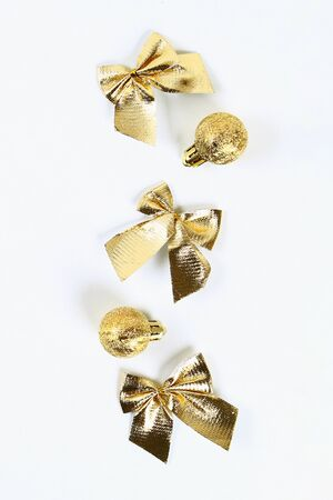 Christmas layout. Golden toy ball, bow on a white background. New Year 2020, christmas, winter concept. top view, flat lay composition
