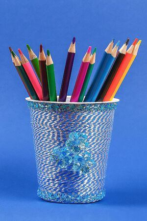Diy pencil holder plastic glass sour cream, yogurt wrapped thread blue background. Decoration flower hot glue, decorative sticky tape. Gift idea. Step by step. Top view. Process kid childrens craft Stok Fotoğraf