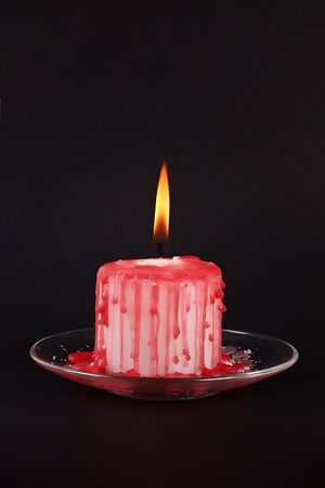 DIY Halloween white candle covered in red wax like blood drops on black background. Gift idea, decor Halloween. Step by step. Top view. Process kid children Halloween craft. Workshop.