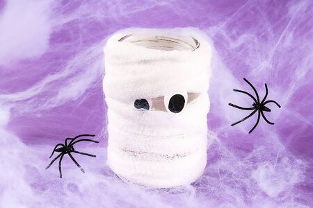 Halloween holiday concept. White spider web with two black spider web purple background. Diy mummy out of a bandage.