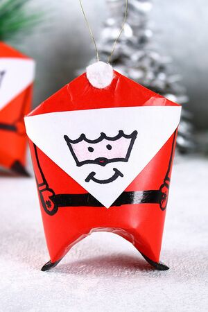 Christmas Santa Claus made from toilet paper hub, colored paper, marker, glue, fishing line and cotton pad. DIY toy on the Christmas tree. Handmade Guide, step by step. Christmas decor Stok Fotoğraf