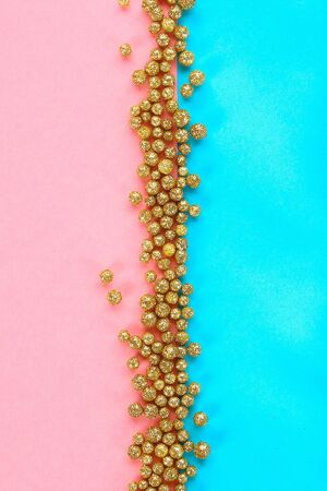 Pastel background decorated with shiny decorative stars and balls. Top view.