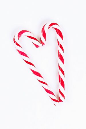 Christmas layout. Striped red-white cane candies on a white background. New Year 2020, christmas, winter concept. top view, flat lay composition