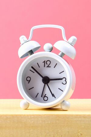 White small alarm clock on a wooden shelf on pink pastel background. Minimalism