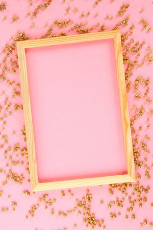A wooden empty frame on a pastel background surrounded by shiny decorative stars and balls. Top view.