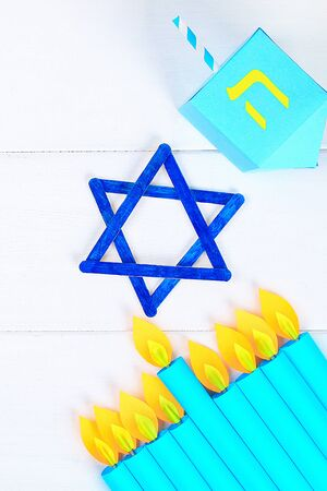 Menorah, dreidel, sevivon, the star of David with their own hands on a white wooden table. DIY for a child. Celebration of Chanukah Zdjęcie Seryjne