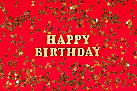 Text Happy birthday laid out of gold letters on a beautiful background. Golden stars confetti. Zdjęcie Seryjne