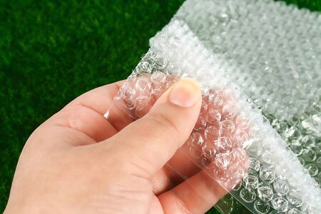 The hand touches the plastic wrap. The concept of touch, tactility, feelings.
