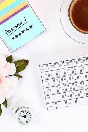 The password on the sticker is a note on the white desktop next to the coffee mug and the keyboard. Top view, flat layout