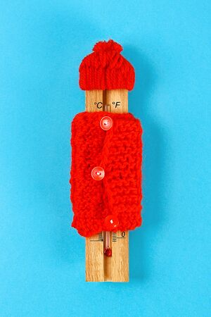 Wooden thermometer, wearing a red hat and sweater on a blue background. The concept of cold, frost, low temperature.